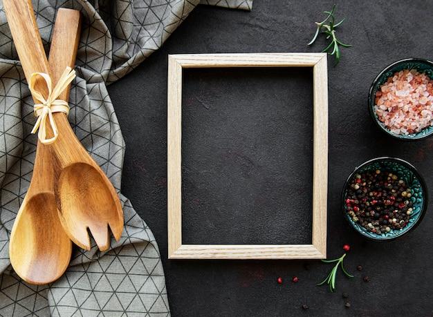 Utensílios de cozinha de madeira antigos e especiarias com moldura como borda em uma mesa preta