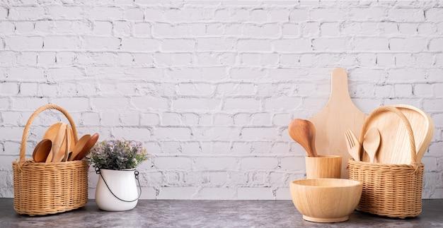 Utensílios de cozinha de madeira colocados na textura da parede de tijolo branco