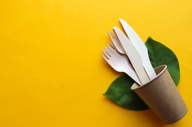 Utensílios de cozinha de madeira descartáveis ecológicos em fundo amarelo. facas, garfos e um copo de papel. o conceito de desperdício zero. conceito de ecologia.