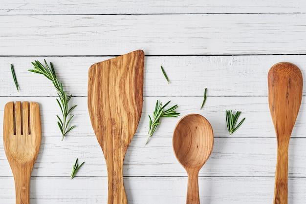 Utensílios de cozinha de madeira e alecrim em um fundo branco de madeira, vista superior