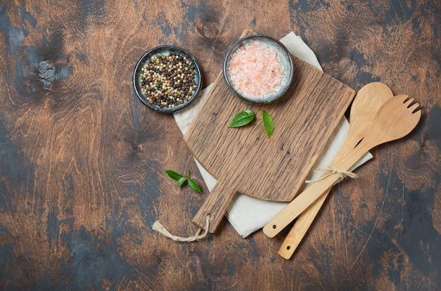 Utensílios de cozinha de madeira e especiarias. colheres de madeira, tábua, guardanapo e especiarias em uma velha mesa de madeira.