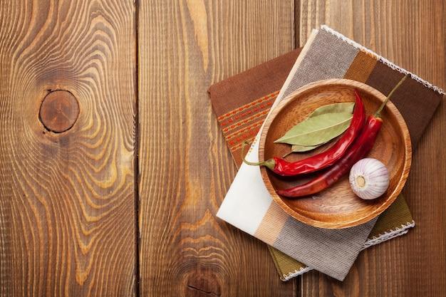 Utensílios de cozinha de madeira e temperos sobre fundo de mesa de madeira com espaço de cópia