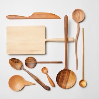 Utensílios de cozinha de madeira em fundo branco. tábua de corte, garfo, faca e colher