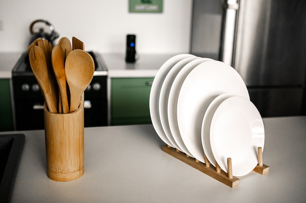 Utensílios de cozinha de madeira em um copo de madeira no fundo de uma bela cozinha moderna estante branca com conjunto de louça