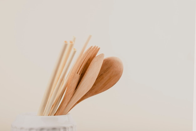 Utensílios de cozinha de madeira reutilizáveis, garfo, faca, colher, tubos de trigo. conceito de desperdício zero, itens ecológicos.