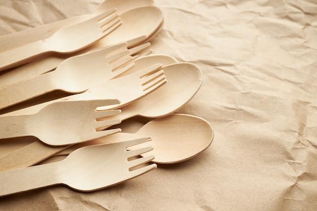 Utensílios de cozinha descartáveis ecológicos em fundo de papel. olhe de cima. garfos e colheres de madeira. conceito ecológico