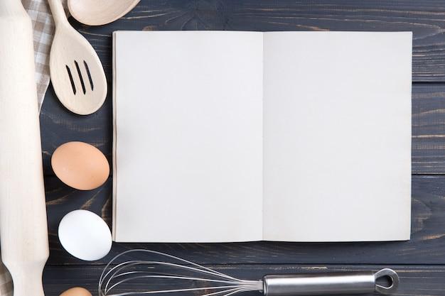 Utensílios de cozinha e livro branco em branco aberto na mesa de madeira