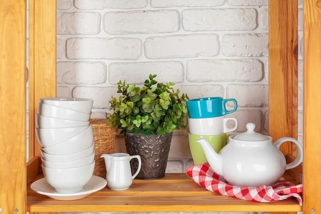 Utensílios de cozinha e louça na prateleira de madeira