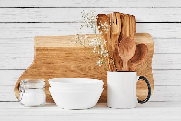 Utensílios de cozinha e tábua de corte na mesa branca