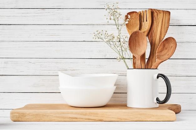 Utensílios de cozinha e tábua na mesa branca
