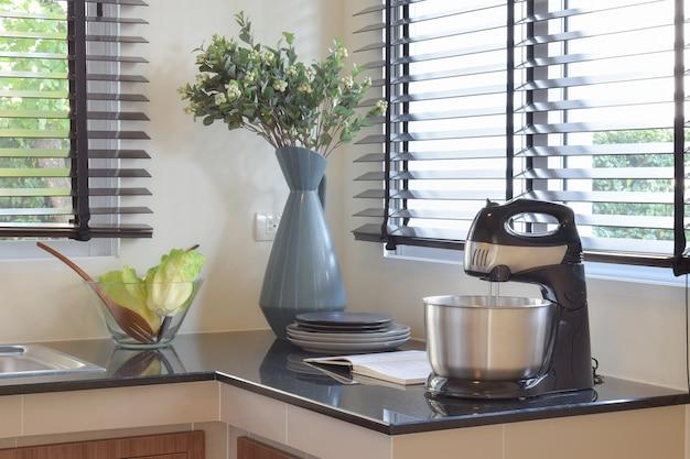 Utensílios de cozinha e utensílios cerâmicos modernos na bancada do granito preto