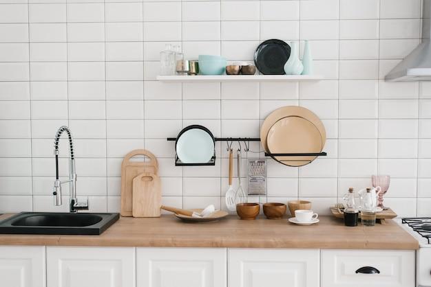 Utensílios de cozinha e utensílios na cozinha de madeira branca brilhante