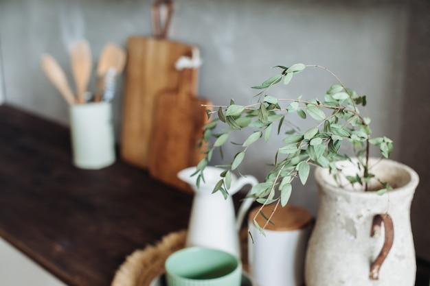 Utensílios de cozinha em cima de uma mesa de madeira, contra uma parede texturizada cinza. espigas secas. vaso em primeiro plano