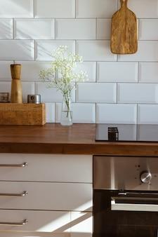 Utensílios de cozinha em latão, acessórios de chef. cozinha suspensa com parede de azulejos brancos e mesa de madeira. flores brancas no fundo da cozinha vista lateral da luz de manhã cedo