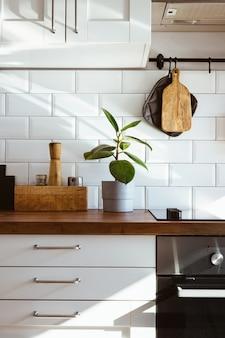 Utensílios de cozinha em latão, acessórios de chef. cozinha suspensa com parede de azulejos brancos e mesa de madeira. planta verde no fundo da cozinha vista lateral da luz de manhã cedo