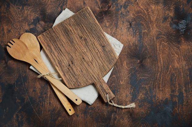 Utensílios de cozinha em madeira. colheres de madeira, tábua, guardanapo em uma velha mesa de madeira.