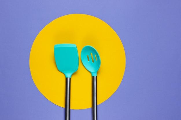 Utensílios de cozinha em roxo com um círculo amarelo no meio