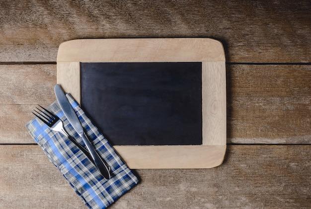 Utensílios de cozinha em um quadro negro com um guardanapo xadrez azul