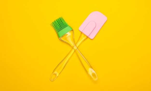 Utensílios de cozinha. espátula de cozinha e pincele em um amarelo. minimalismo.