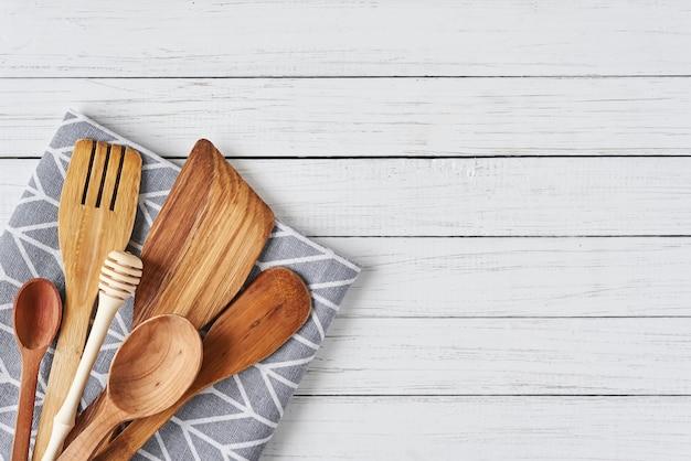 Utensílios de cozinha, espátula e toalha em um fundo branco de madeira com espaço de cópia