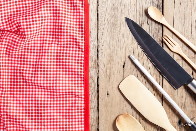 Utensílios de cozinha, faca, colher de pau na mesa de madeira velha e toalha de mesa vermelha com espaço de cópia.