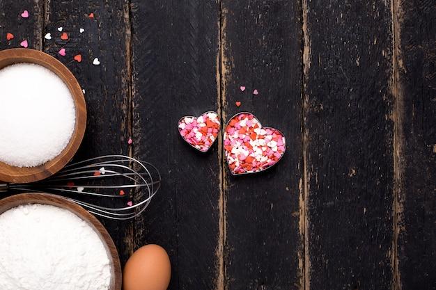 Utensílios de cozinha, farinha, corações e açúcar na madeira