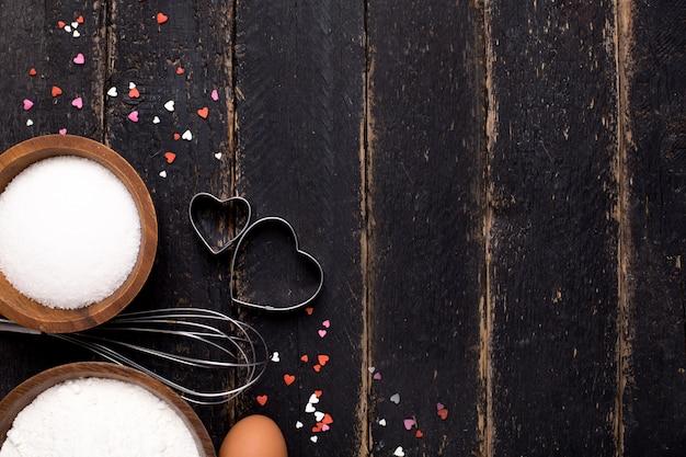 Utensílios de cozinha, farinha e açúcar na madeira