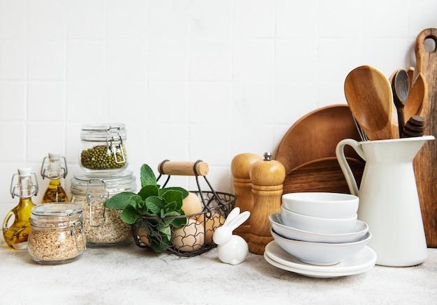 Utensílios de cozinha, ferramentas e louças na superfície da parede de azulejos brancos