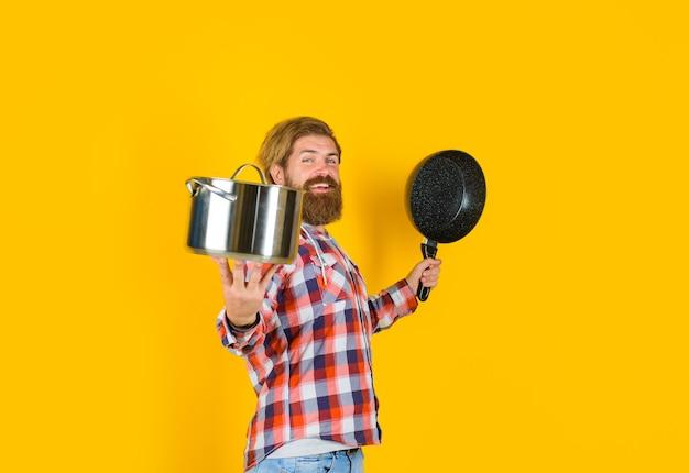 Utensílios de cozinha homem barbudo com panela frigideira homem chef com panela panela cozinhando utensílios de cozinha