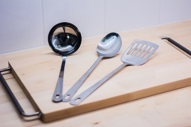 Utensílios de cozinha inox na placa de madeira