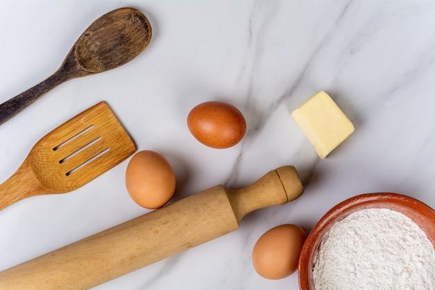 Utensílios de cozinha, ovos, farinha e manteiga.