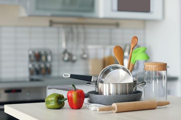 Utensílios de cozinha, panelas e pimentões na mesa de madeira