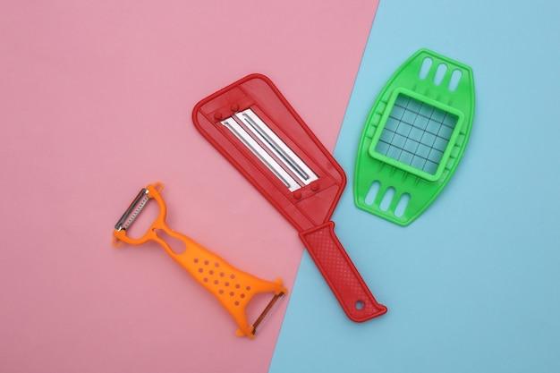 Utensílios de cozinha para cortar legumes e faca para descascar a pele em fundo rosa azul. vista do topo