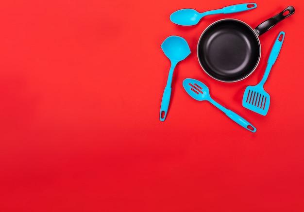 Utensílios de cozinha para cozinhar na cozinha isolada com copyspace no vermelho