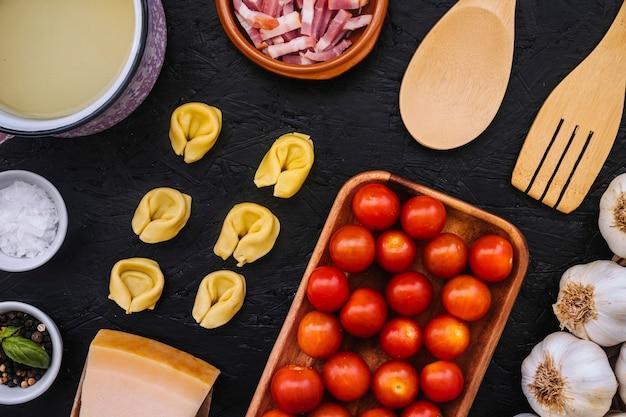 Utensílios de cozinha perto de ingredientes de massa