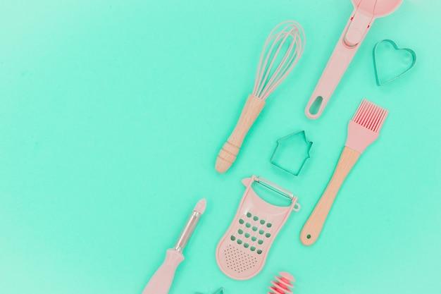 Utensílios de cozinha rosa. forma de cozimento maior, bata e ferro. vista do topo