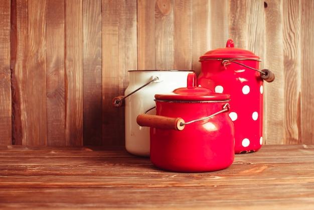 Utensílios de cozinha vintage vermelhos e brancos em uma mesa branca