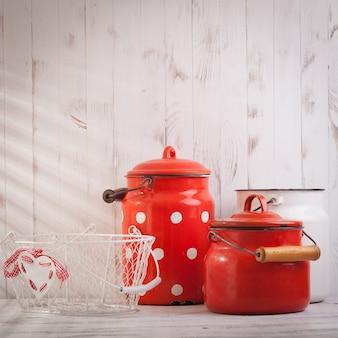 Utensílios de cozinha vintage vermelhos e brancos em uma talha branca