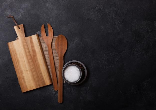 Utensílios de madeira de cozinha vintage com tábua na mesa de pedra preta. vista do topo.