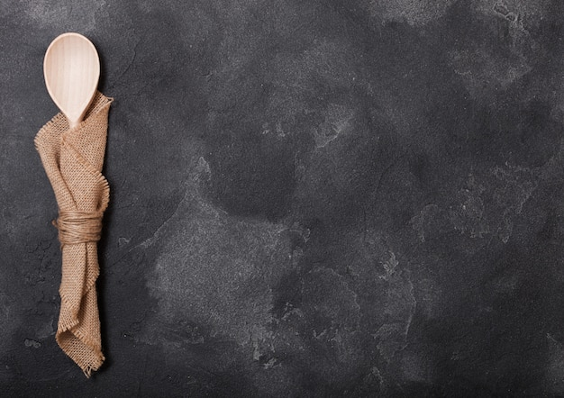 Utensílios de madeira de cozinha vintage na mesa de pedra preta. vista do topo..