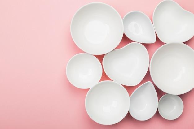 Utensílios de mesa brancos limpos na cor-de-rosa. vista de cima, copie o espaço