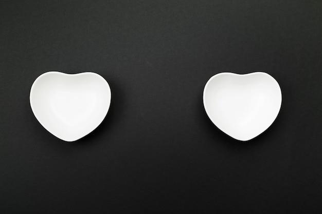 Utensílios de mesa brancos limpos no formulário do coração no preto. vista de cima, copie o espaço