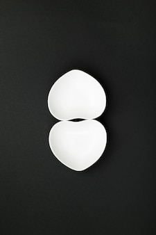Utensílios de mesa brancos limpos no formulário do coração no preto. vista do topo