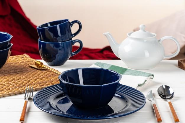 Utensílios de mesa de cerâmicos azuis clássicos na toalha de mesa quadriculada close-up