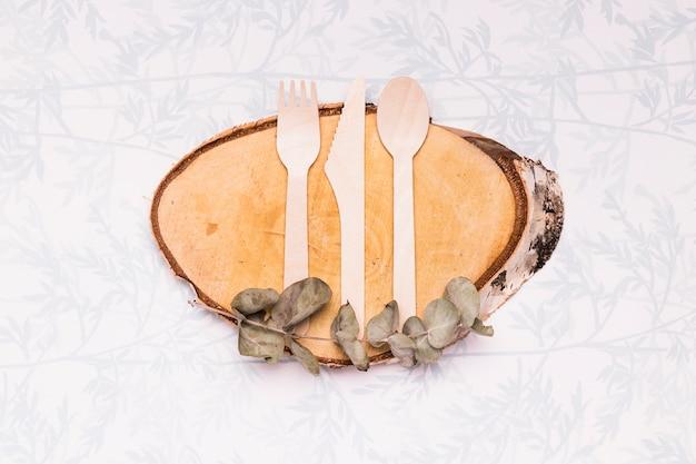 Utensílios de mesa de madeira na placa de madeira