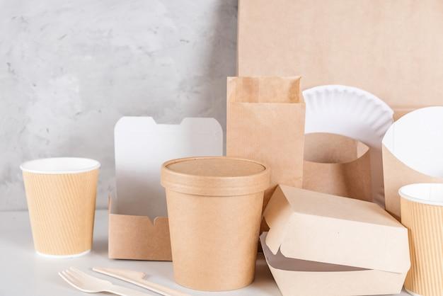 Utensílios de mesa descartáveis ecológicos. copos de papel, pratos, sacolas, recipientes de fast food e talheres de madeira de bambu