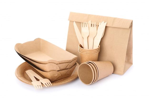 Utensílios de mesa e saco de papel amigáveis de eco isolados no branco. pratos descartáveis Foto Premium