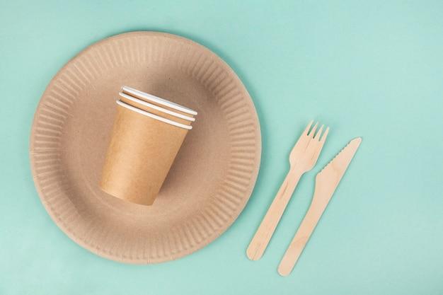 Utensílios de mesa ecológicos sobre fundo azul, pratos e copos de papel, garfos e nomes de madeira, vista de cima