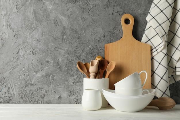Utensílios de mesa, talheres e placa de madeira na mesa branca contra um fundo cinza, espaço para texto