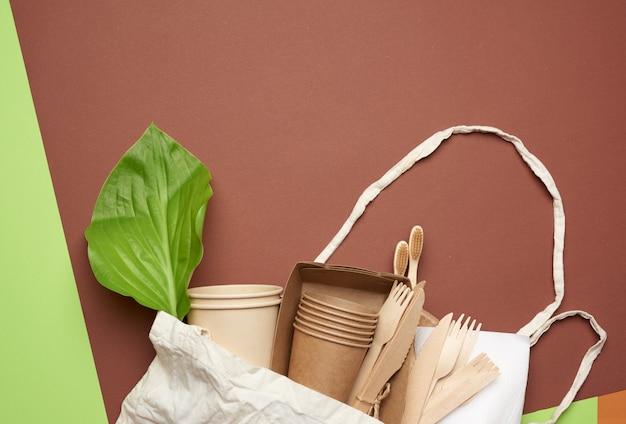 Utensílios de papel descartáveis de papel artesanal marrom e materiais reciclados em um fundo marrom